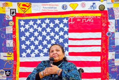 Cable Hoover/Independent Cecelia Fred sits in front of a quilt that was made in her honor as she gives a speech during a luncheon at the San Juan Center for Independence in Gallup Wednesday.