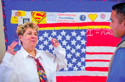 Cable Hoover/Independent Cecelia Quintana, left, explains to Echohawk Lefthand how she made a flag and quilt to honor her friend Cecelia Fred in Gallup Wednesday.